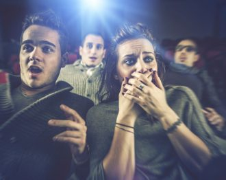 Couple scared at the cinema, watching horror movie