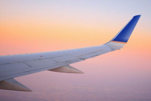 A view from an airplane window -- with focus on the plane's wing -- during a colorful, pastel sunrise.