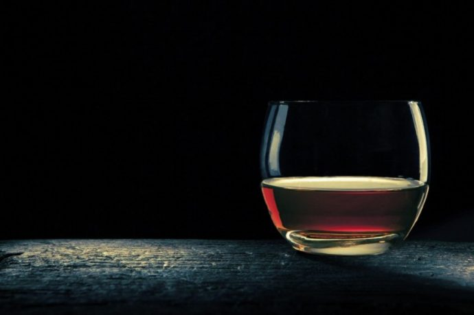 great rounded glass with bourbon on a old wood table, with black background