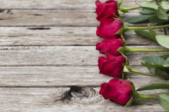 Five red roses on wooden background, selective focus