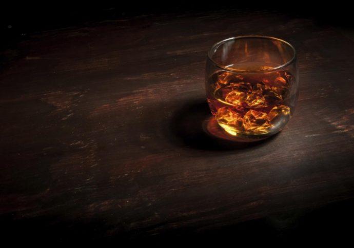 Glass of whiskey on a dark wood bar.