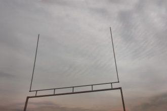 looking up at American football goalpost