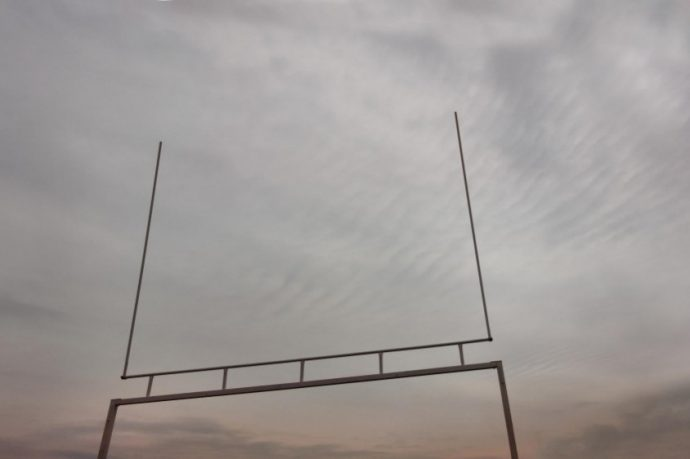 looking up at American football goalpost