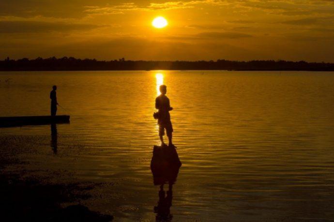 Two Silhouette Fishermen fishing in the lake.Fishermen fishing on a boat silhouette.