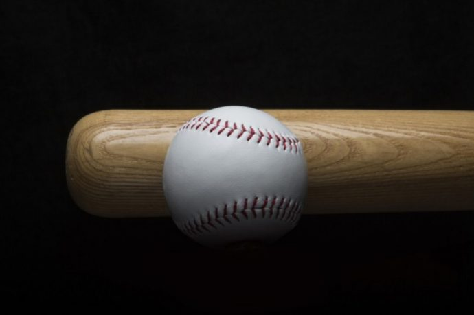 Lets play baseball and all you need is a bat. Close up photo of a bat and a ball
