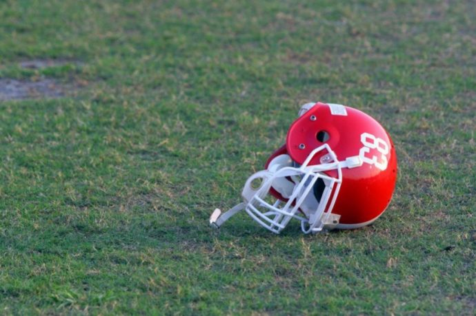 Red football helmet with white numbers laying upside down on green grass of football field.