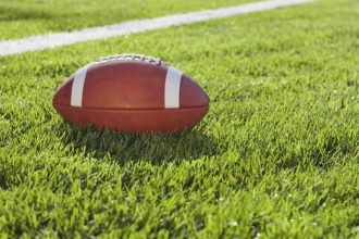 An official college football sits on a grass field in afternoon sunlight